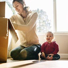 mom packing moving boxes with baby in background